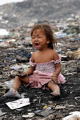 Child sitting in the middle of a dump.
